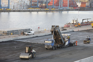 Heavy duty paver laying RCC with backdrop of Tilbury Container Port